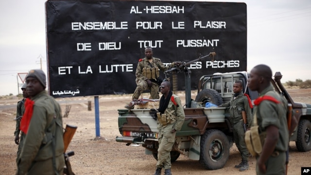 "Malian soldiers are stationed at the entrance of of Gao, northern Mali, Jan. 28, 2013. The sign, a reminder of Islamic extremists, reads ""Al Hesbah, together for the pleasure of God almighty and the struggle against sins."""