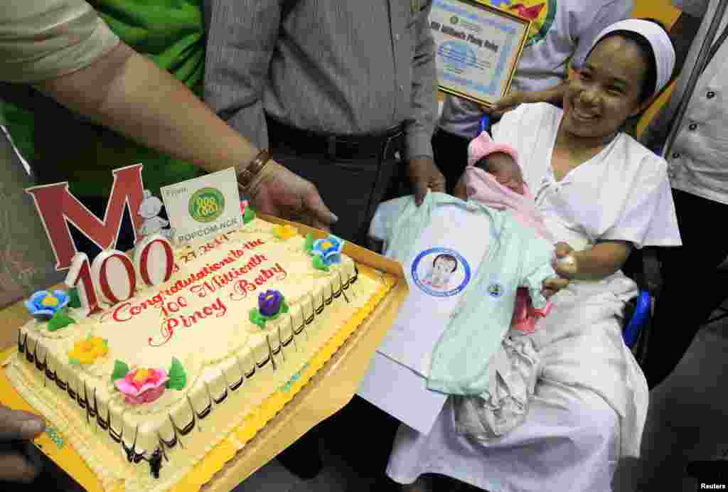 Dailin Duras Cabigayan, 27, smiles as she cradles her newly born baby girl, Chonalyn, as government health officials present her with a cake and clothing as the 100 millionth baby born into the Philippines' population during a short ceremony inside the Jose Fabella hospital in Manila.