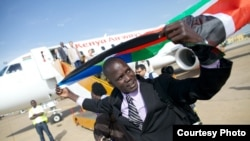 Olympic athlete and former refugee Guor Marial raises the flag of South Sudan after returning to the country.
