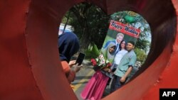 Sepasang kekasih di Solo, berfoto di depan poster Pangeran Harry dan istrinya, Meghan Markle, 20 Mei 2018. (Foto: AFP)