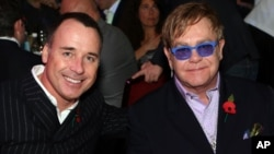 FILE - Sir Elton John (R) and David Furnish are seen at an awards ceremony in London, Nov. 5, 2012.