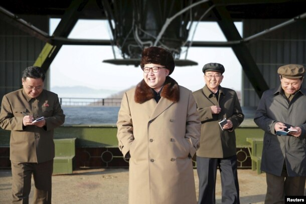 North Korea leader Kim Jong Un smiles as he visits Sohae Space Center in Cholsan County, North Pyongan province for the testing of a new engine for an intercontinental ballistic missile in this undated photo.