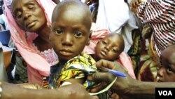 Un travailleur de la santé examinant un enfant soupçonné de souffrir de malnutrition (Photo N. Palus/VOA)