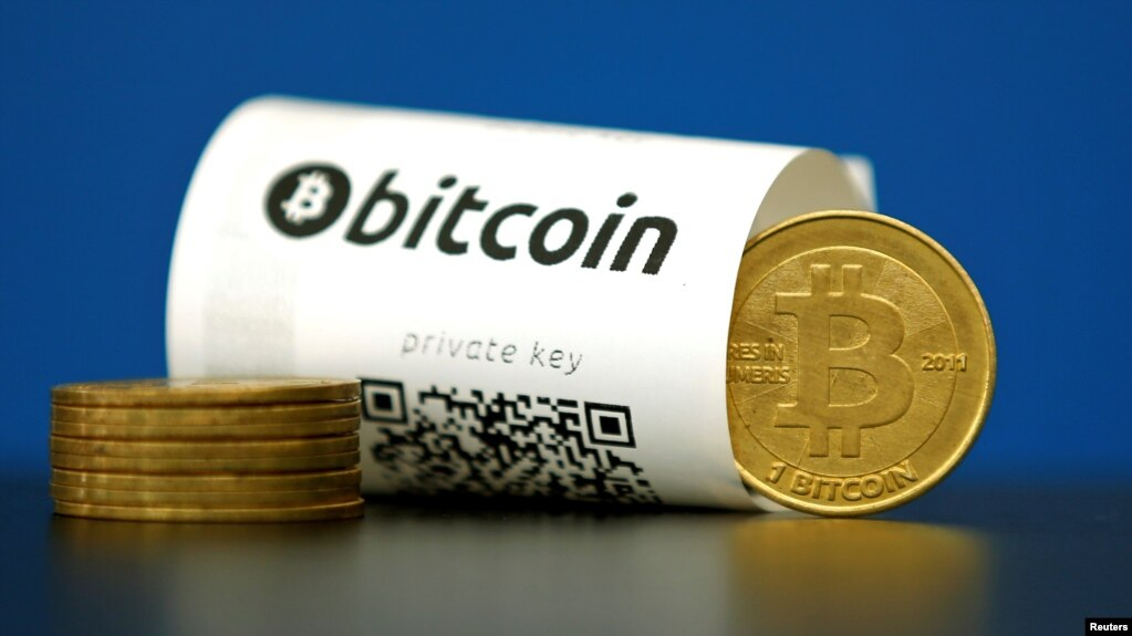 A Bitcoin paper wallet with QR codes and a coin are seen at La Maison du Bitcoin in Paris, May 27, 2015.