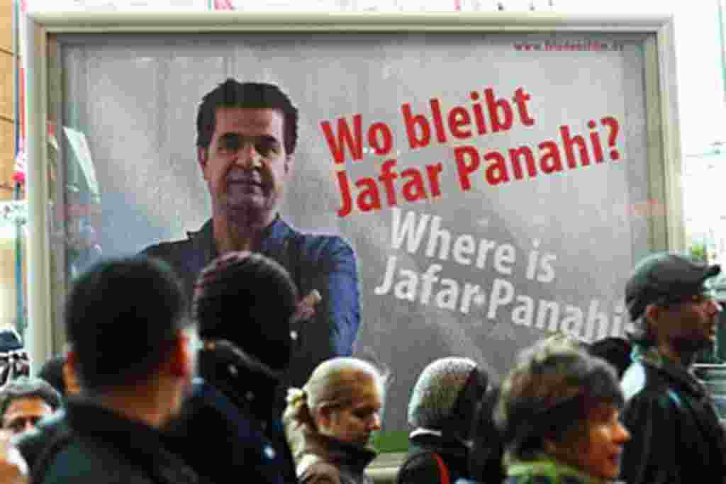 People walk in front of a poster showing Iranian filmmaker Jafar Panahi prior to the screening of the movie 'Offside' by Jajar Panahi at the International Film Festival Berlinale in Berlin, Germany, February 11, 2011
