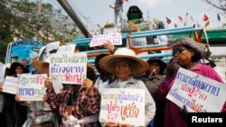 Farmers hold signs in front of a combine harvester during a rally demanding the Yingluck administration resolve delays in payment from the rice-pledging scheme outside the Commerce Ministry in Nonthaburi province, on the outskirts of Bangkok, Feb. 6, 2014