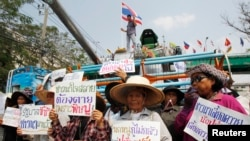 Petani membawa poster dalam sebuah protes meminta pemerintahan Yingluck segera membayar skema beras mereka di pinggiran Bangkok, 6 Februari 2014