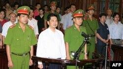 Tiến sĩ luật Cù Huy Hà Vũ đứng giữa 2 công an tại phiên tòa ở Hà Nội, ngày 2 tháng 8, 2011.