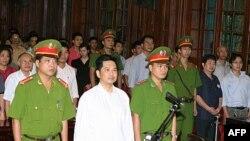 Tiến sĩ Cù Huy Hà Vũ đứng giữa 2 công an tại phiên tòa ở Hà Nội hôm 2 tháng 8, 2011
