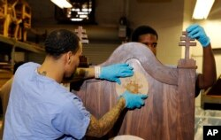 FILE - Inmates Evan Davis, left, and Rameen Perrin fix a cross and plaque on a chair carved out of walnut for Pope Francis to use during his planned visit to the Curran-Fromhold Correctional Facility in Philadelphia, Aug. 24, 2015.