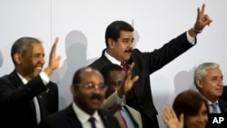 Venezuela's President Nicolas Maduro, center top, flashes a sign during the VII Summit of the Americas' official group photo in Panama City, Panama, April 11, 2015.