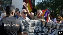 Protesters shout behind a banner showing photos of Spanish Civil War victims, outside the Supreme Court in Madrid, Spain, Tuesday, Sept. 24, 2019. (AP Photo/Paul White)
