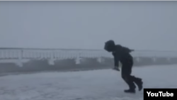 Video Screenshot of man getting blown around in strong winds