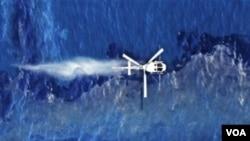 Un helicópero arroja dispersante sobre la mancha de petróleo que ha dejado el derrame del barco liberaino Rena en Nueva Zelanda.