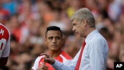 L'entraineur d'Arsenal Arsène Wenger (droite) donne des instructions à sa nouvelle recrue Alexis Sanchez pour son premier match avec le club, lors de la Coupe des Emirats de football entre Arsenal et Benfica au Arsenal's Emirates Stadium de Londres, le 2 aout 2014. (AP Photo/Matt Dunham).