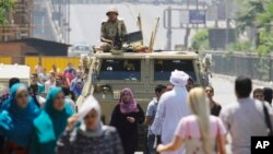 Seorang tentara Mesir berjaga dengan kendaraan lapis baja dekat lapangan Nahda, tempat para pendukung Presiden terguling Mohammad Morsi berkemah di sekitar Universitas Kairo, Giza (12/8).