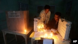 Polling officials check voting materials by candlelight next to electronic voting machines at a voting center on the eve of the second phase of Indian parliamentary elections at Senapati in north eastern Manipur state, India, Tuesday, April 8, 2014. India