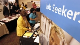 People walk by recruiters at a jobs fair in the Pittsburgh suburb of Green Tree, Pennsylvania, July 10, 2012.