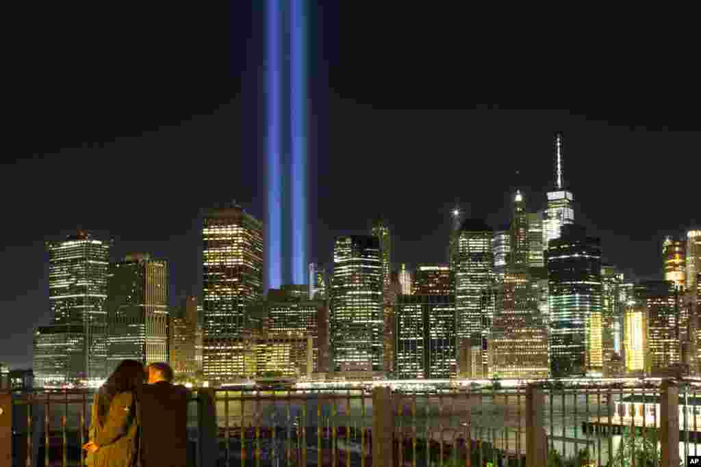 A couple embraces on the Brooklyn Promenade as the Tribute in Light rises above the lower Manhattan skyline in New York, Sept. 10, 2017.