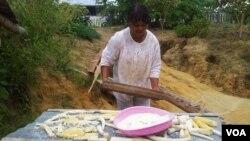 Seorang transmigran di Poso, Sulawesi Tengah, menjemur ubi kayu. (Photo: VOA)