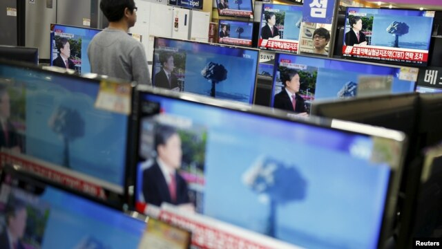 A sales assistant watches TV sets broadcasting a news report on North Korea's nuclear test, in Seoul, Jan. 6, 2016.