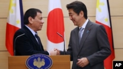 PM Jepang Shinzo Abe (kanan) dan tamunya Presiden Filipina Rodrigo Duterte berjabat tangan sebelum memberikan konferensi pers bersama di Tokyo, Rabu (26/10).