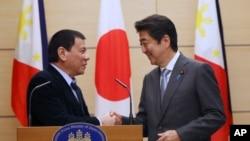 2016年10月26日菲律宾总统杜特尔特(左)和日本首相安倍晋三在东京记者会上握手