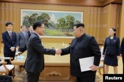Pemimpin Korea Utara Kim Jong-un berjabat tangan dengan Chung Eui-yong yang memimpin delegasi Korea Selatan, dalam foto yang dirilis kantor berita pemerintah Korea Utara (KCNA), 6 Maret 2018.
