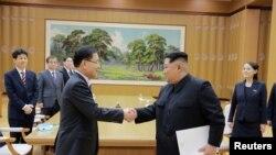 Pemimpin Korea Utara Kim Jong Un berjabat tangan dengan Chung Eui-yong yang memimpin delegasi Korea Selatan, dalam foto yang dirilis kantor berita pemerintah Korea Utara (KCNA), 6 Maret 2018.