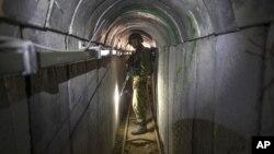 Isroil askari Xamas guruhi qazigani aytilayotgan tunnelni ko'zdan kechirmoqda, 25-iyul, 2014-yil.