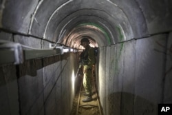 FILE - In this July 25, 2014, photo, an Israeli army officer gives journalists a tour of a tunnel allegedly used by Palestinian militants for cross-border attacks, at the Israel-Gaza Border.