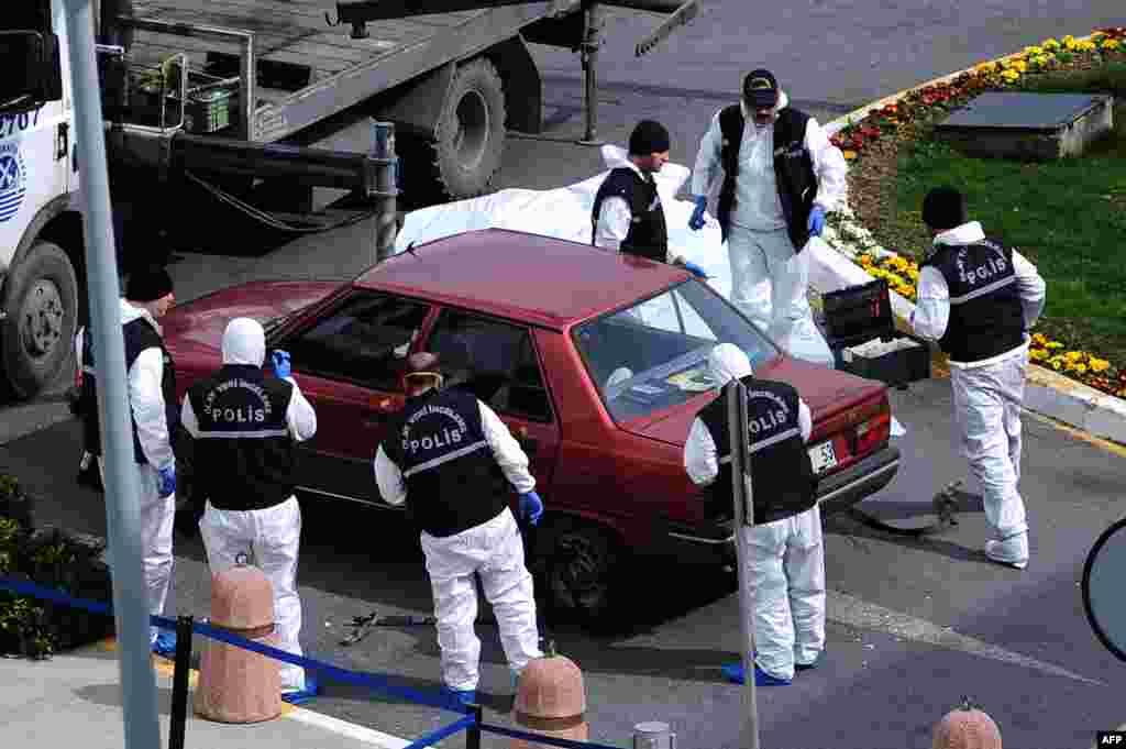 Turkish forensic officers prepare to remove a vehicle in front of the US consulate in Istanbul. Police detained one man after he threatened to detonate a bomb he said he was carrying. Bomb experts discovered he was not carrying a bomb.