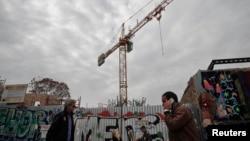 Warga melewati proyek konstruksi di Athena.