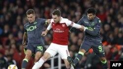 Gelandang Arsenal, Aaron Ramsey (tengah), menahan pemain depan Sporting asal Argentina, Marcos Acuna (kanan) saat penyisihan grup Piala UEFA antara Arsenal dan Sporting Lisbon di Stadion Emirates, London, 8 November 2018.
