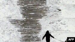Một người cùng với con chó đi trong một công viên phủ tuyết trong thủ đô Bucharest của Romania