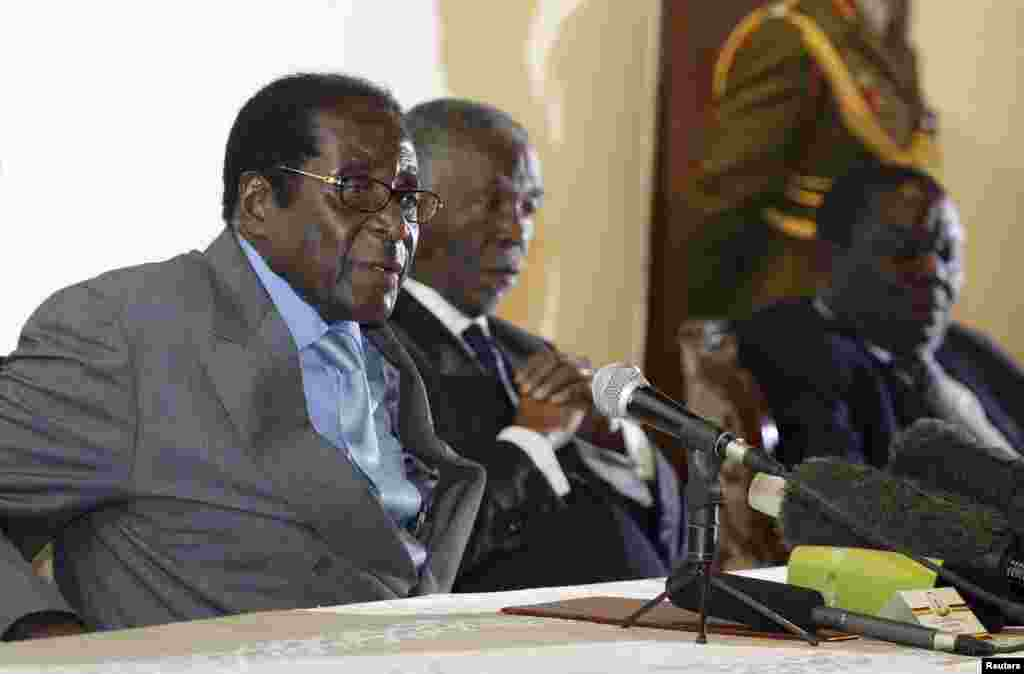 Zimbabwe's President Robert Mugabe (L) addresses the media as South Africa's President Thabo Mbeki (C) and leader of Zimbabwe's main opposition Movement for Democratic Change (MDC) Morgan Tsvangirai listen at Harare's Rainbow Towers Hotel July 21, 2008.