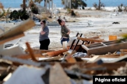 Christina Amanda, right, and Connie Huff, wait for an insurance adjuster as they look for their possessions at the site of their destroyed home in the aftermath of Hurricane Michael in Mexico Beach, Fla., Oct. 17, 2018.