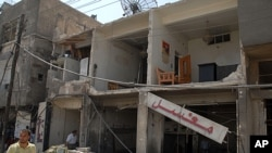 Các tòa nhà, cửa hàng bị hư hại nghiêm trọng sau vụ nổ bom ở Qazaz hôm 10/5/12
