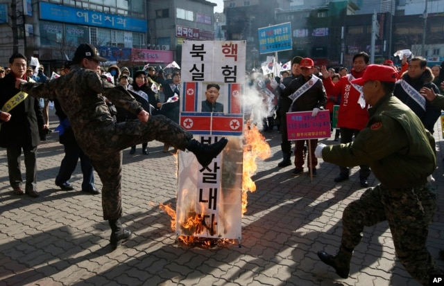 A member of a South Korean conservative group kicks a burning banner with image of North Korean leader Kim Jong Un and North Korean flags during a rally denouncing the North, in Paju, South Korea, Jan. 11, 2016.