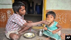 "An Indian boy feeds his sister at their home in a slum in Hyderabad. Levels of under-nutrition in the country were ""unacceptably high"" despite impressive GDP growth, Prime Minister Manmohan Singh said Tuesday and added that the problem of malnutrition wa"