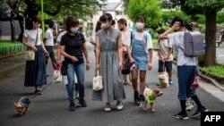 """Anggota """"Patroli Wan-Wan"""" lokal, Keiko Shimizu (depan kiri) dengan Yorkshire Terrier betinanya (bawah kiri), Marika Igarashi (C) dan Yurika Igarashi (kedua dari kanan) dengan pudel """"Sakura"""" berjalan menuju sebuah sekolah dasar di Tokyo< Jepang, 14 Juli 2021. (AFP)"""