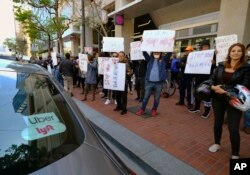 Uber and Lyft drivers demonstrate outside of Uber headquarters, May 8, 2019, in San Francisco.