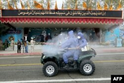 A handout picture provided by Iranian army official website on April 17, 2020 shows Iranian army soldiers wearing protective clothes and holding disinfection equipment against the coronavirus COVID-19 during the Iran army day parade in Tehran.
