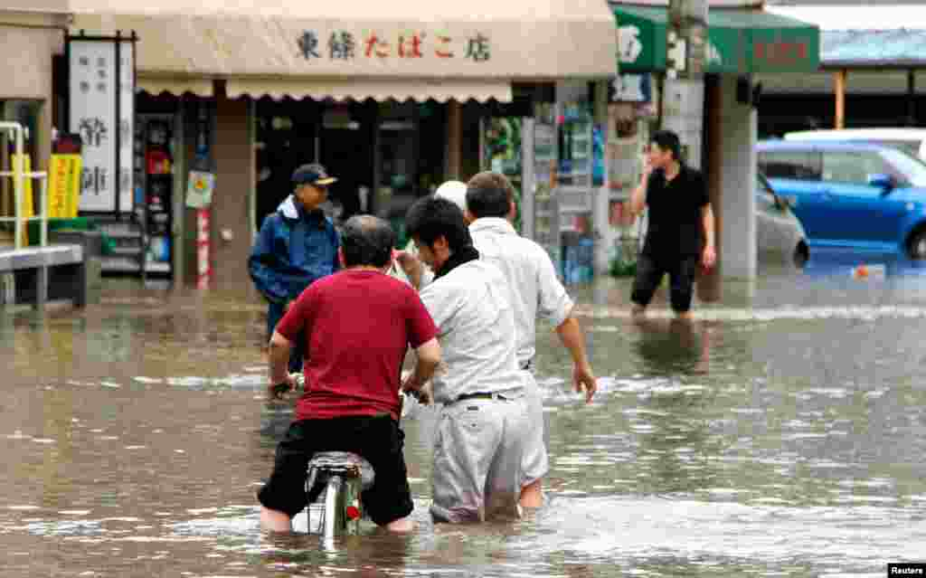 People wade through a flooded street caused by heavy rains in Kumamoto, southwestern Japan.