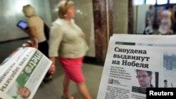 Một người phát báo cho khách bộ hành, trong thủ đô Moscow, Nga, có đăng tin về Edward Snowden trên một trang của tờ báo, 2/7/13