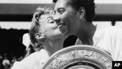 Althea Gibson holds the Wimbledon women's singles trophy as she gets a kiss from Darlene Hard, whom she defeated at Wimbledon in England in this July 6, 1957 file photo.