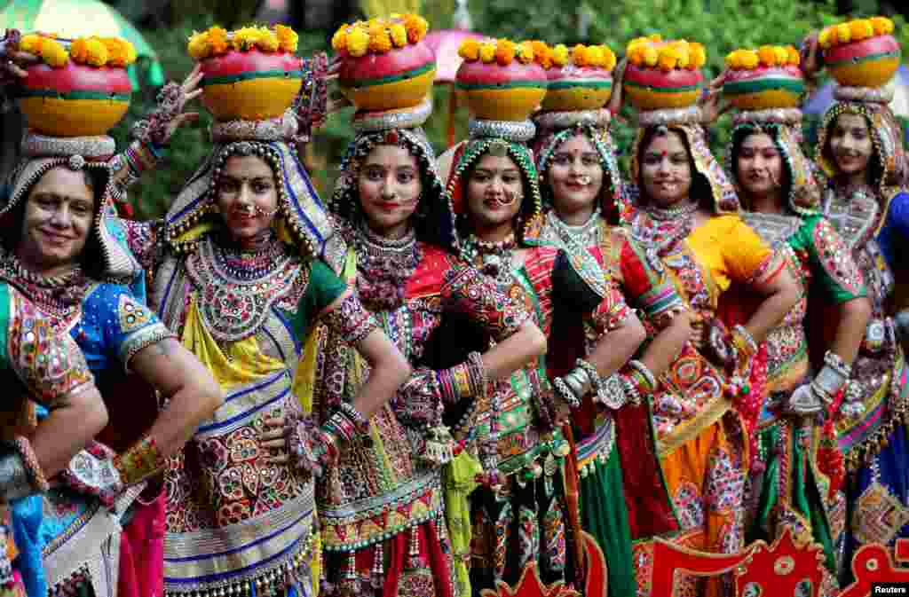 Women pose for pictures during rehearsals for Garba, a folk dance, ahead of Navratri, a festival during which devotees worship the Hindu goddess Durga and youths dance in traditional costumes, in Ahmedabad, India.