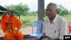 FILE - Meas Muth, right, sits next to a Buddhist monk at Anlong Veng district in Oddar Mean Chey province, Cambodia, July 23, 2006. Meas Muth was implicated in the 1975 Mayaguez incident in which at least 38 U.S. servicemen died.