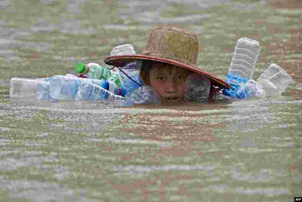 A boy swims in floodwaters at Kyaut Ye village near the Hinthada town in Myanmar's Irrawaddy Delta region.