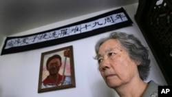 """资料照:由天安门镇压事件死难者家属组成的 """"天安门母亲""""的创始人丁子霖站在儿子蒋捷连的遗像前。大学生蒋捷连在六四镇压期间被打死,年仅19岁。(2008年6月4日)"""